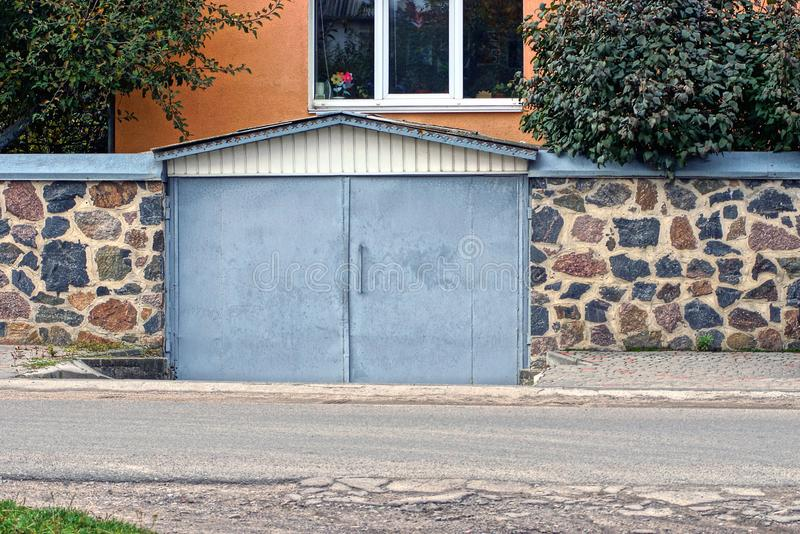 Garage with gray metal gates and a stone fence on the street royalty free stock image