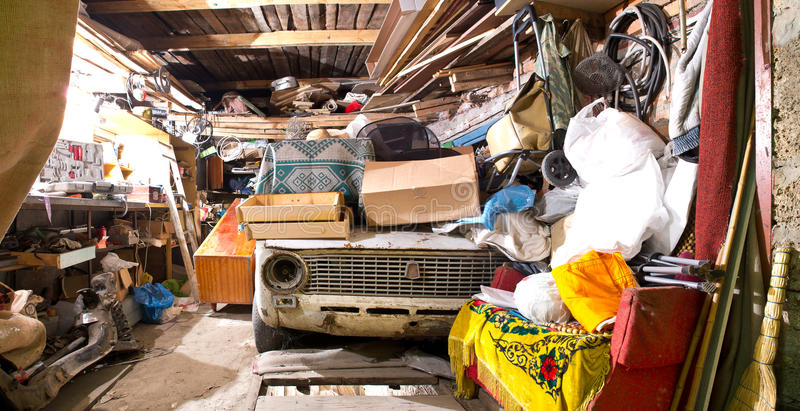 Garage inside. Old broken car, shelves with tools and stacks of things stock image
