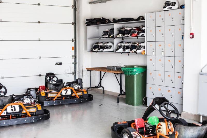 Garage pour le stockage karting, étagères avec des casques et boîtes de rangement Été, amusement actif de famille ou sports photos stock