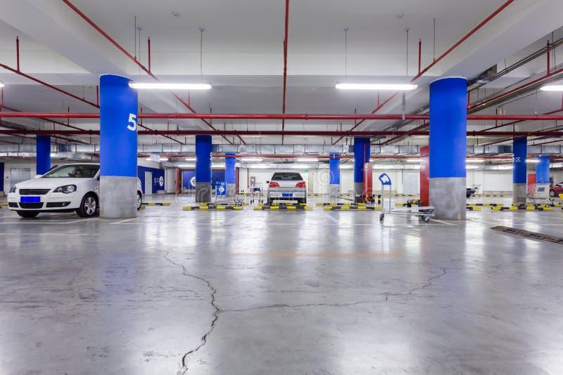 Garage, sous terre intérieur avec quelques voitures garées images libres de droits