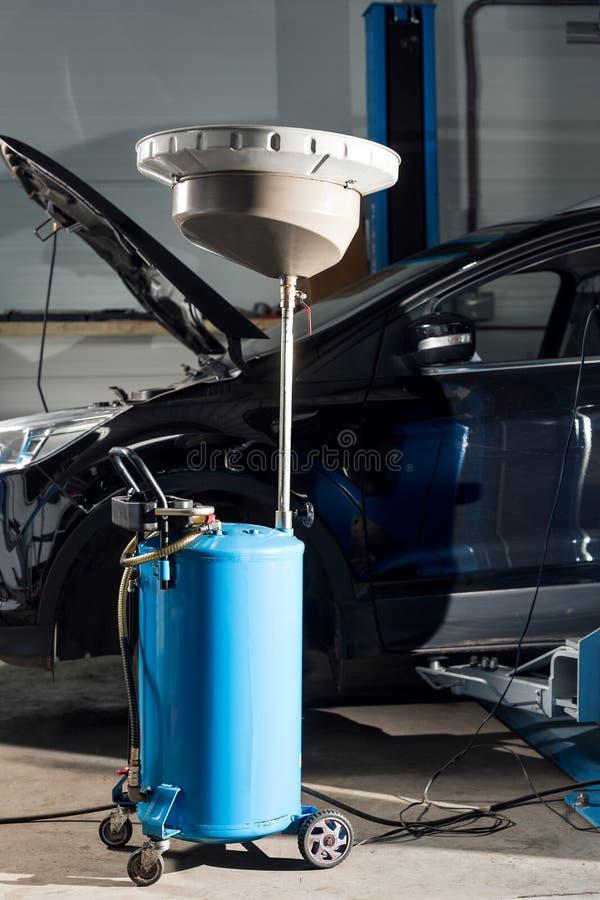 Garage vide de réparation automatique, mécanicien de attente de travail changeant l'huile d'une voiture à un magasin auto photos libres de droits