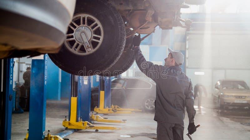 Garagebilservice - en mekaniker kontrollerar överföringen fotografering för bildbyråer