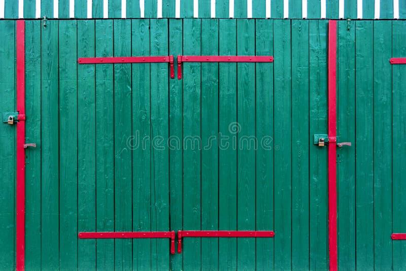 Garagedörrarna i gräsplan dekoreras med ljusa röda metallmellanlägg och vita slats arkivbilder