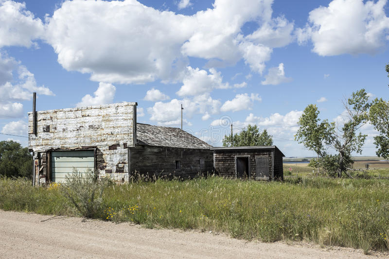 Garagem abandonada velha que senta-se na grama alta imagem de stock