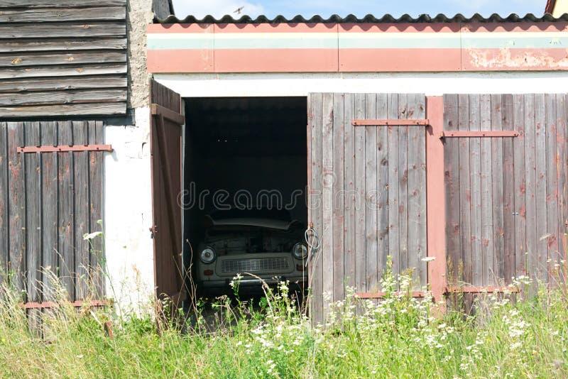 Garagem arruinada velha com o carro do vintage através do estar aberto imagens de stock