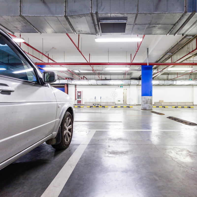 Garagem de estacionamento, no subsolo interior com alguns carros estacionados imagem de stock royalty free