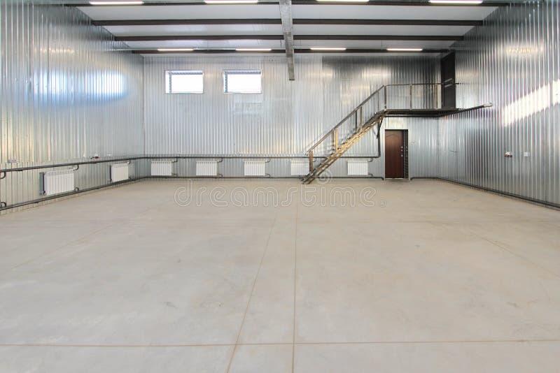 A garagem de estacionamento vazia, armazena o interior com as grandes portas e janelas brancas para dentro fotos de stock royalty free