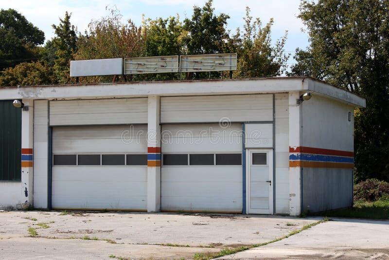Garagem do serviço do carro abandonada por proprietários após a saída do negócio com sinais de néon quebrados na fachada superior imagem de stock royalty free