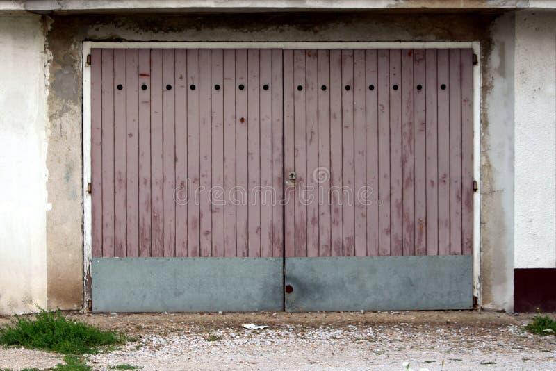 Garagentoren gemacht von verfallenen hölzernen Brettern mit dem Metallplattenregenschutz angebracht an gebrochener alter Wand lizenzfreie stockfotografie