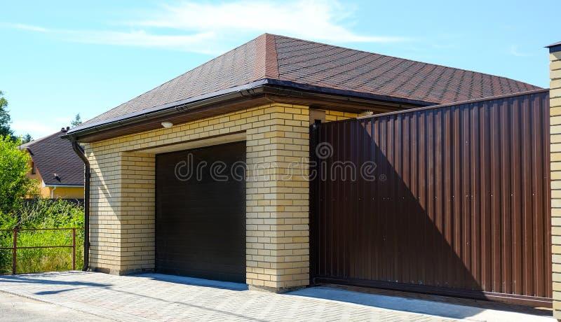 Garaje para los coches Puerta de desplazamiento a la casa Verdor hermoso de la cabaña del verano en el jardín fotografía de archivo