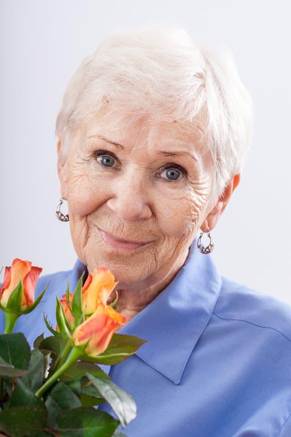 Garandma with birthday flowers. A closeup of a grandma holding a birthday bunch of roses royalty free stock photos
