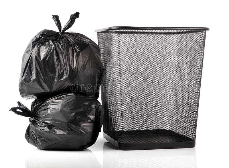 Garbage bags. Black garbage bags with empty trash bin isolated on white background royalty free stock photos