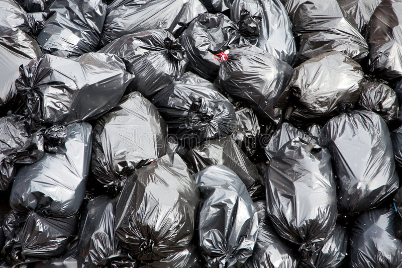 Garbage bags. A pile of black garbage bags with tons of trash stock photos