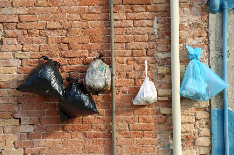 Garbage bags hanging on the wall of the houses to prevent the ra stock photos