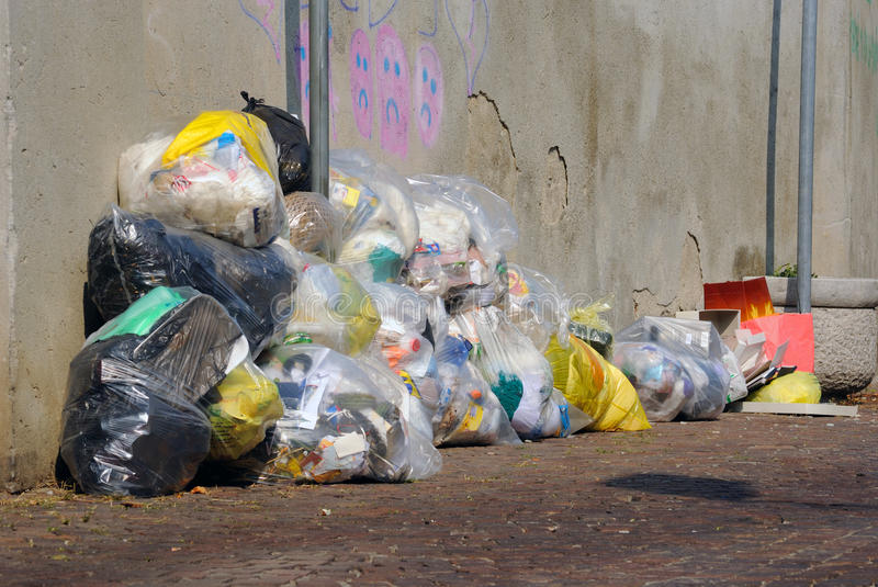 Garbage bags. A pile of transparent plastic garbage bags sitting near a wall stock photo