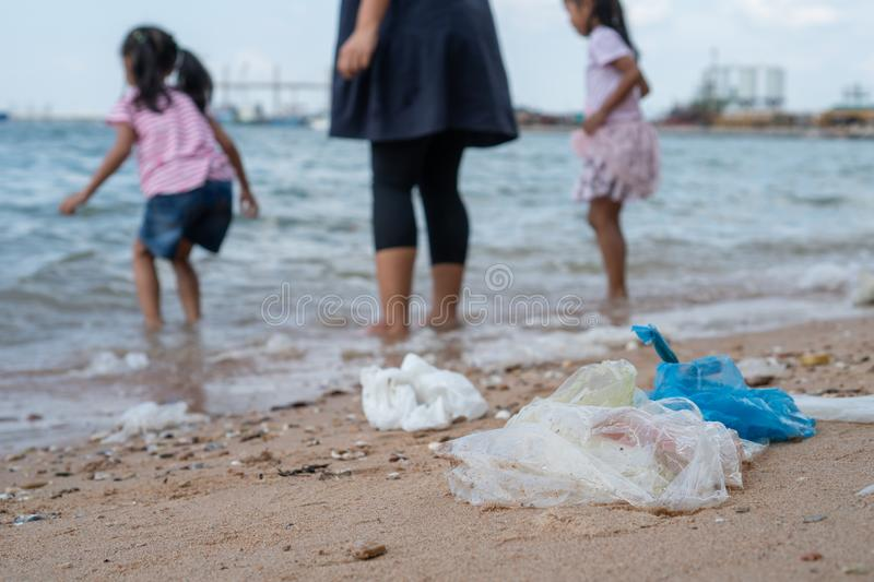 Garbage on the beach with family playing water in the sea on background, environmental pollution of sea royalty free stock image