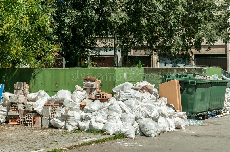 Big pile and stack of garbage and junk in the plastic bags near dumpster cans on the street in the city stock photo