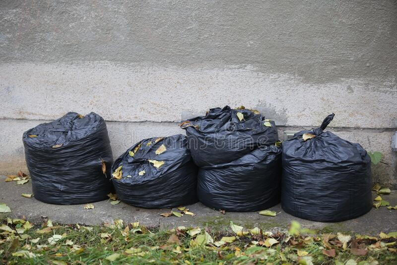 Garbage in black plastic bags royalty free stock photo