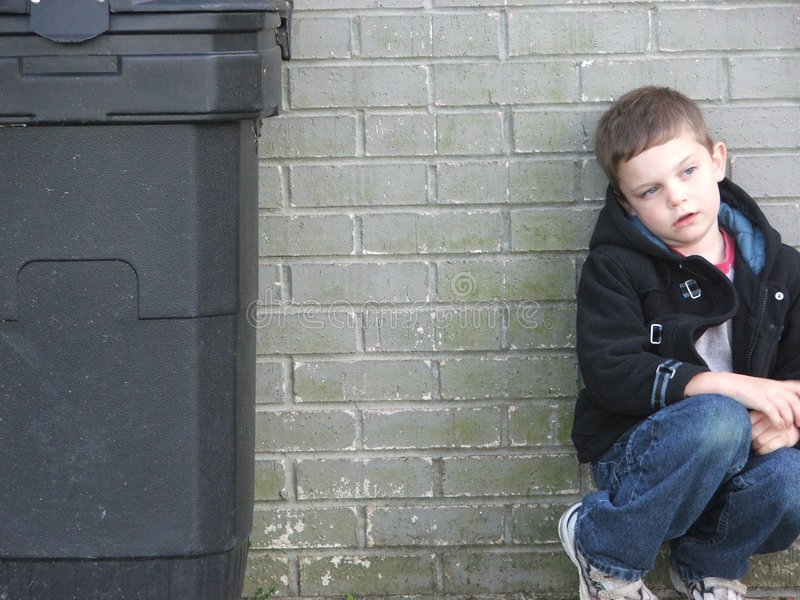 Garbage Can Kid. Young boy against a brick wall, next to a garbage container stock photo
