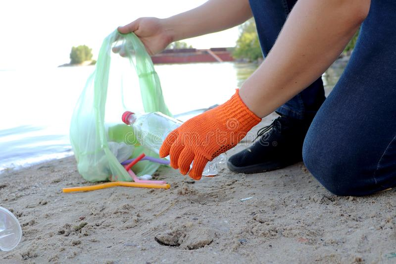 Garbage collection on the beach. Plastic and packages scattered on the beach. A man collects plastic. Ecology protection concept stock image