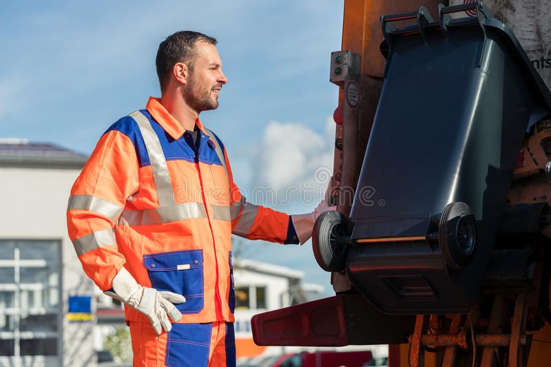 Garbage collection worker putting bin into waste truck royalty free stock photo