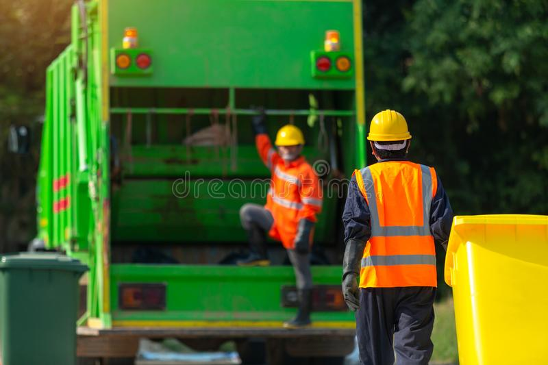 [garbage collector] Asian worker of urban municipal recycling garbage collector truck loading waste and trash bin in thailand, stock images