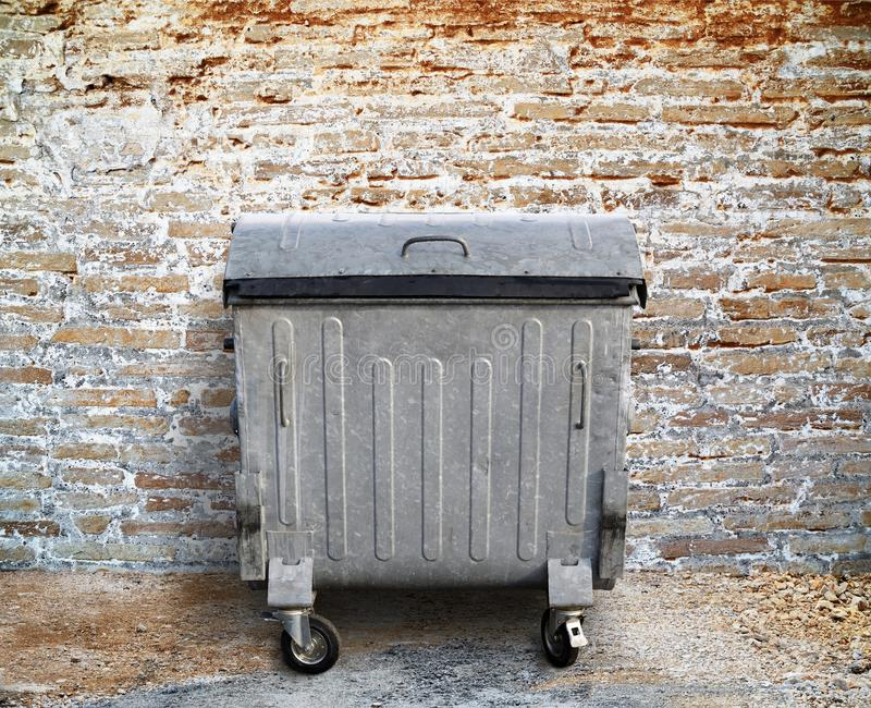Garbage container. With brick wall background royalty free stock photo