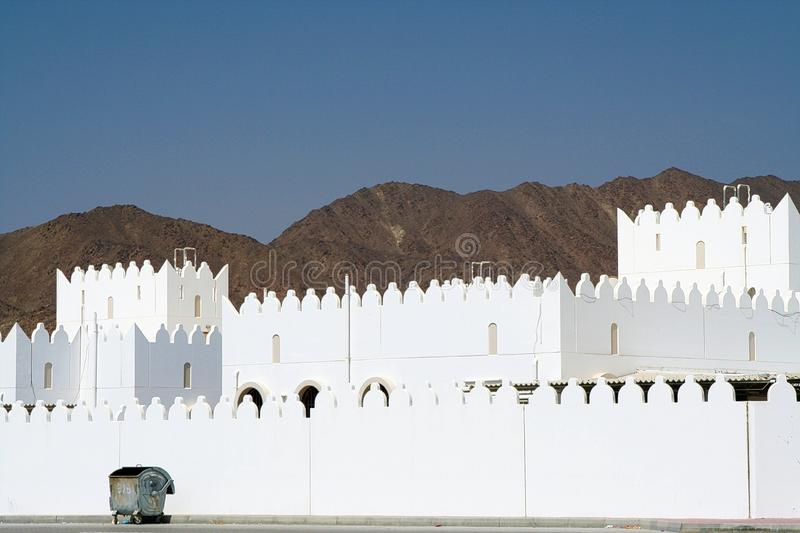 garbage container in front of white house with battlement wall and barren mountain background, Oman royalty free stock photo