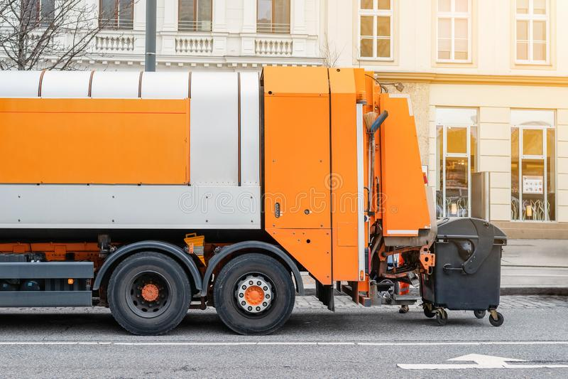 Garbage disposal lorry at city street. Waste dump truck on town road. Municipal and urban services. Waste management, disposal and royalty free stock images