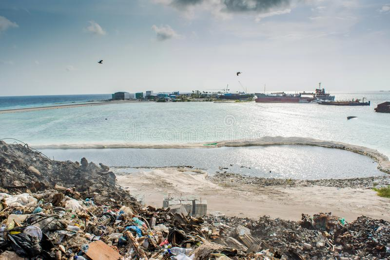 Garbage dump near the ocean full of smoke, litter, plastic bottles,rubbish and trash at the Thilafushi local tropical island stock images