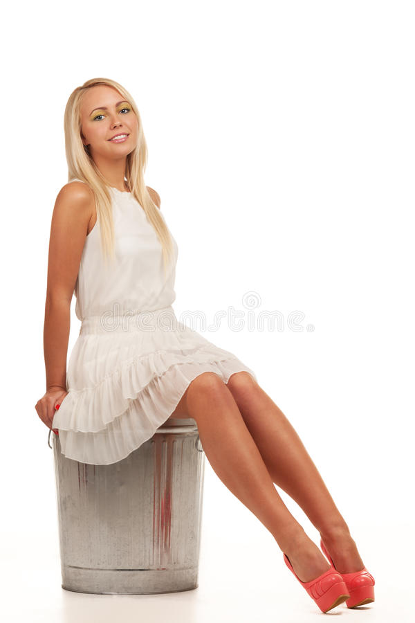 Garbage girl. Smiling girl sitting on a slop bucket royalty free stock image