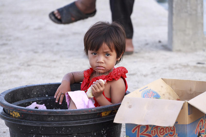 Garbage girl. Poor Indonesian girl sitting in the garbage and holding food royalty free stock photography