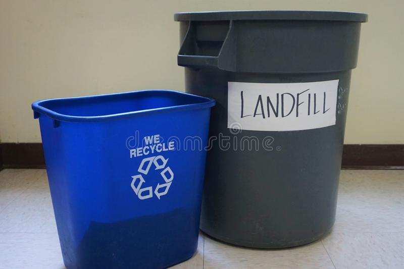 Two plastic bins recycling and landfill. Garbage pail industrial size and smaller blue reduce reuse recycle container compete for items. School oxymoron of stock photos