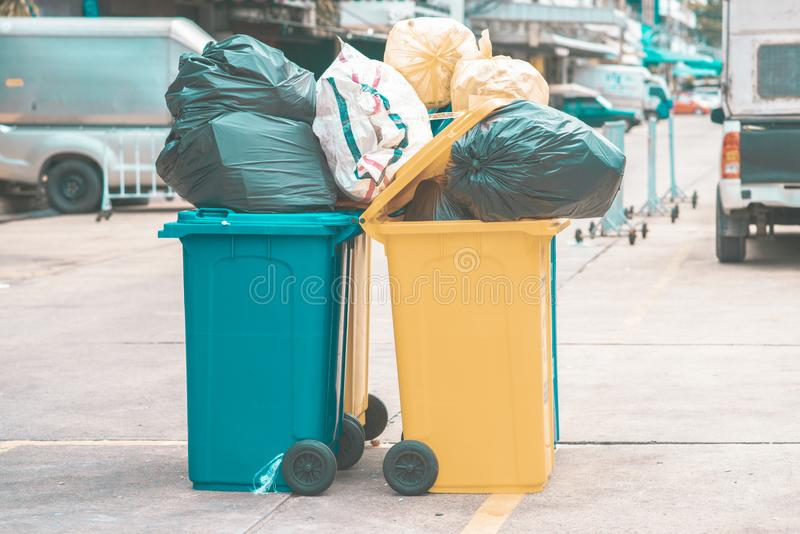 Garbage plastic bags black waste, pollution, lots junk dump, recycle green yellow bin. Many garbage plastic bags black waste, pollution, lots junk dump, recycle royalty free stock photo