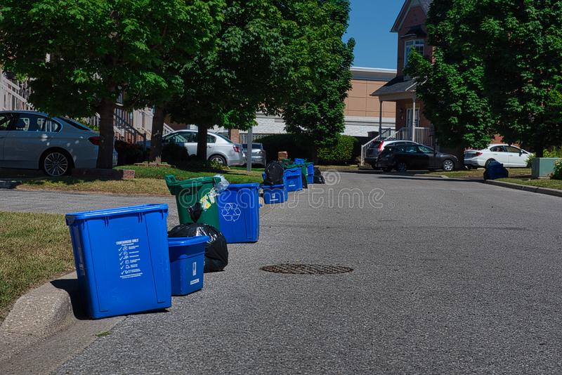 Garbage and recycling pick up day. Garbage, recycling and food waste bins are waiting to be picked up in front of  houses on garbage day stock photos