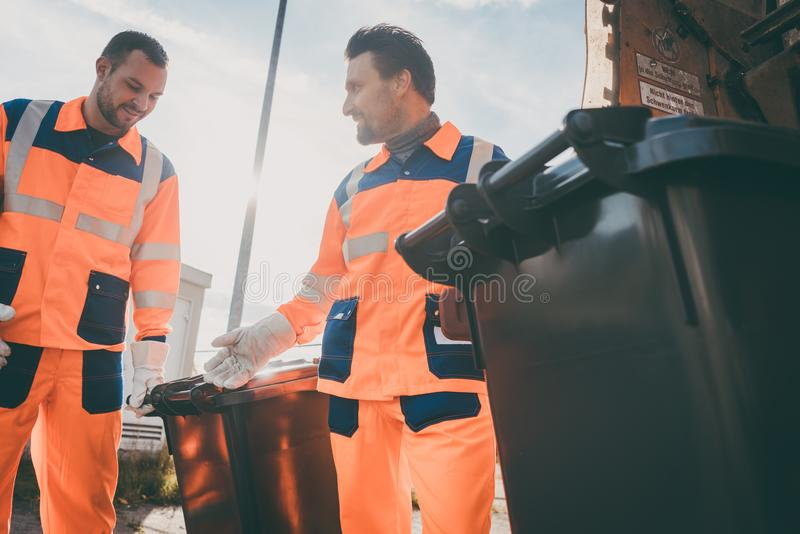 Garbage removal men working for a public utility. Emptying trash container royalty free stock photography