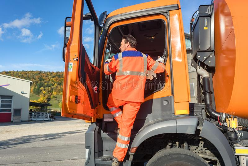 Garbage removal worker getting into the disposal vehicle. Or lorry stock photos