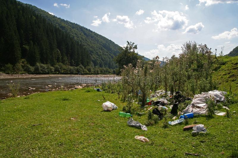 Garbage on the river bank in the mountains royalty free stock photography