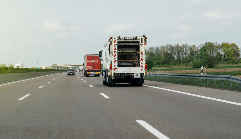 Garbage truck driving fast on highway royalty free stock image