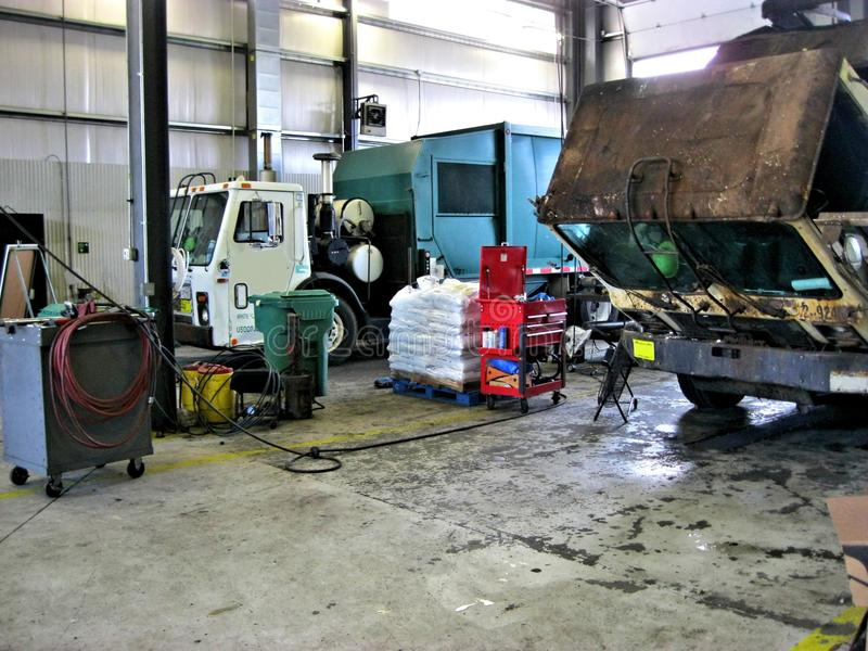 Garbage truck garage. Compacting `packer` waste-hauling trucks in their repair garage. This is a facility where trucks are dispatched from to landfills and royalty free stock photography