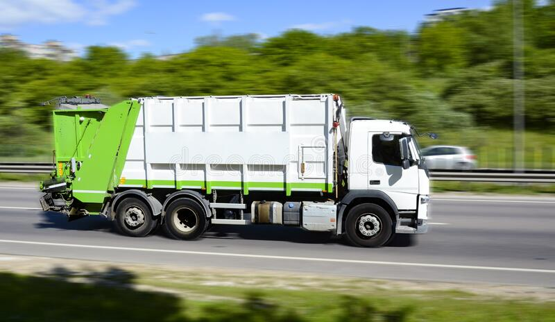 Garbage truck moving fast on the road stock photo