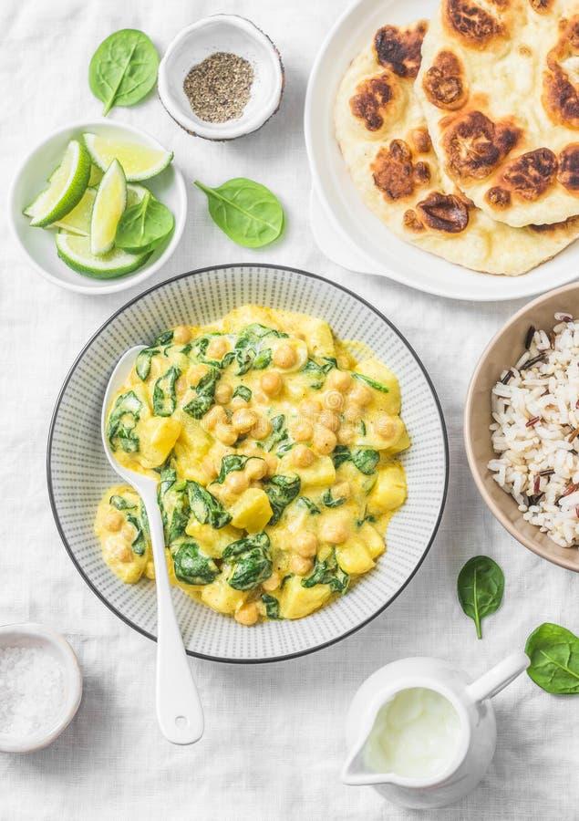 Garbanzo vegetariano, espinaca, curry de la patata, arroz salvaje y flatbread naan en el fondo blanco, visión superior Comida san foto de archivo