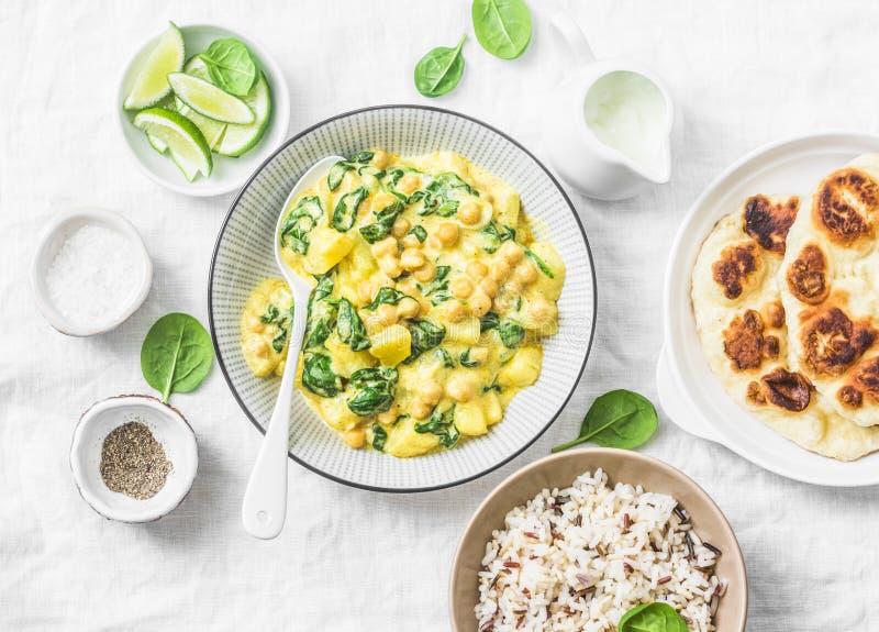 Garbanzo vegetariano, espinaca, curry de la patata, flatbread naan y arroz salvaje en el fondo blanco, visión superior Comida san imagen de archivo