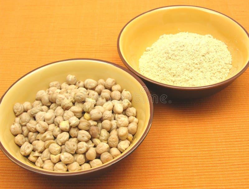 Garbanzos and flour of garbanzos. Two bowls of ceramic with garbanzos and flour of garbanzos royalty free stock photo