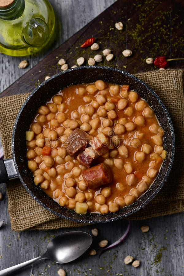 Garbanzos a la riojana, a spanish chickpeas stew. High-angle shot of a stone frypan with garbanzos a la riojana, a spanish chickpeas stew, on a wooden chopping stock photography