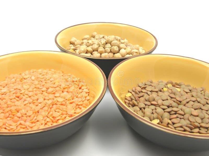 Garbanzos lentils and red lentils. Three bowls of ceramic with garbanzos lentils and red lentils royalty free stock photo