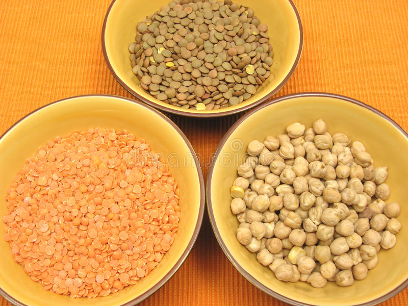 Garbanzos lentils and red lentils. Three bowls of ceramic with garbanzos lentils and red lentils stock photography