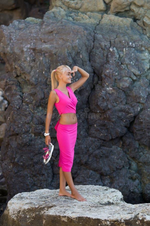 Garbnikująca blond z włosami żeńska osoba odpoczywa przy ustronnym miejscem dziki skalisty seashore fotografia royalty free
