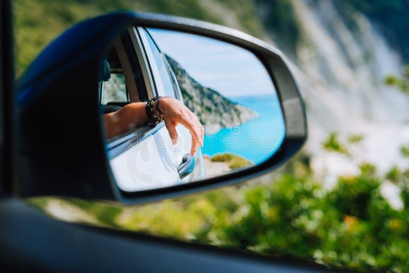 Garbnikująca żeńska ręka w samochodowym bocznego widoku lustrze Błękitny biel skał krajobraz w tle i morze śródziemnomorskie zdjęcie royalty free