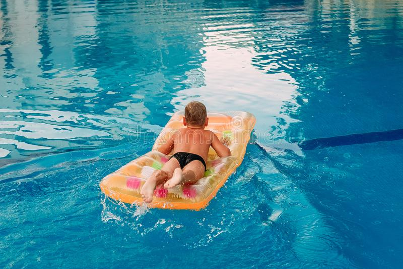 Garbnikująca chłopiec unosi się na jego żołądku na lotniczej materac w plenerowym basenie zdjęcia stock